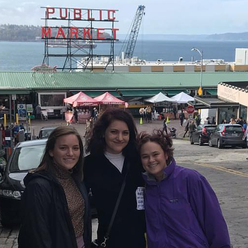 Three women stand in front of Public Market sign in Seattle